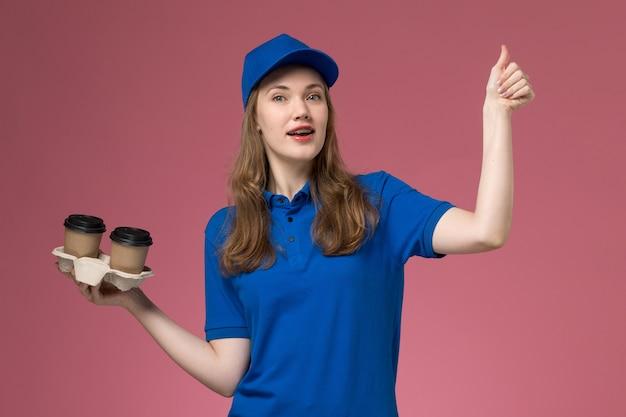 ピンクの背景に茶色の配達コーヒーカップを保持している青い制服の正面図の女性の宅配便サービス制服配達会社の仕事