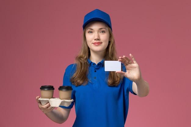 Вид спереди женщина-курьер в синей форме, держащая коричневые кофейные чашки с доставкой, улыбаясь, держа белую карточку на розовом столе, служба доставки униформы
