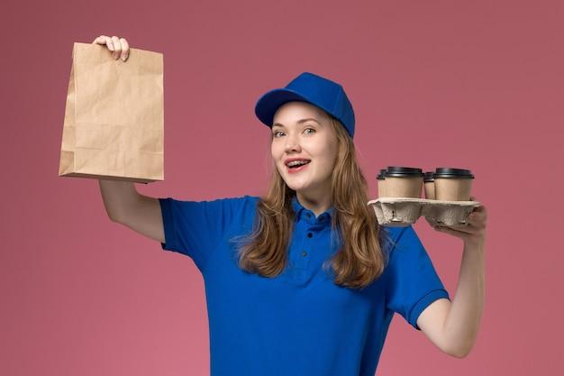 Вид спереди женщина-курьер в синей форме, держащая коричневые кофейные чашки с пакетом еды и улыбку на розовом столе, сервисная форма, работник компании