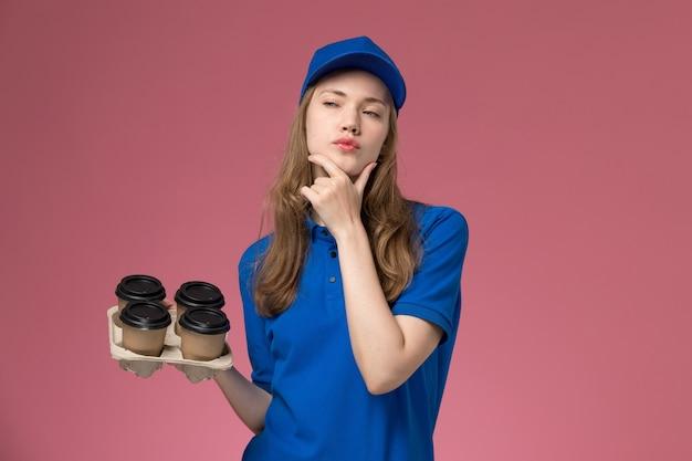 ピンクのデスクサービス制服会社の労働者に思考表現と茶色の配達コーヒーカップを保持している青い制服の正面図女性宅配便