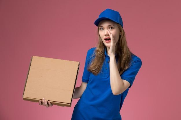 Вид спереди женщина-курьер в синей форме, держащая коробку с едой, шепчет на розовом фоне служба униформы компании