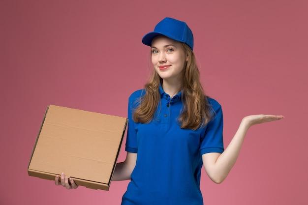 Вид спереди женщина-курьер в синей форме, держащая коробку с едой с красной рукой на розовом фоне, служба униформы компании