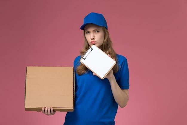 ピンクのデスクサービスの制服の仕事会社で考えている食品配達ボックスとメモ帳を保持している青い制服の正面図女性宅配便
