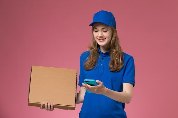 Вид спереди женщина-курьер в синей форме с коробкой для доставки еды и телефоном на розовом столе.