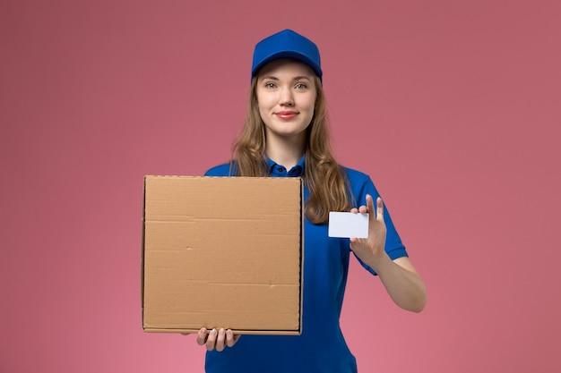 Вид спереди женщина-курьер в синей форме, держащая коробку для доставки еды и белую карточку на розовом столе, сервисная форма, работник компании