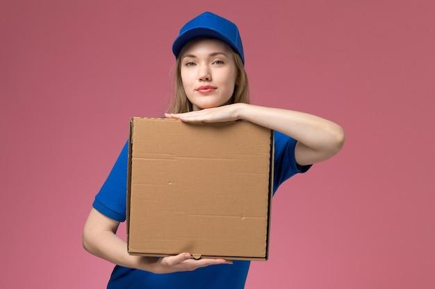 Вид спереди женщина-курьер в синей форме с коробкой для доставки еды на розовом фоне.