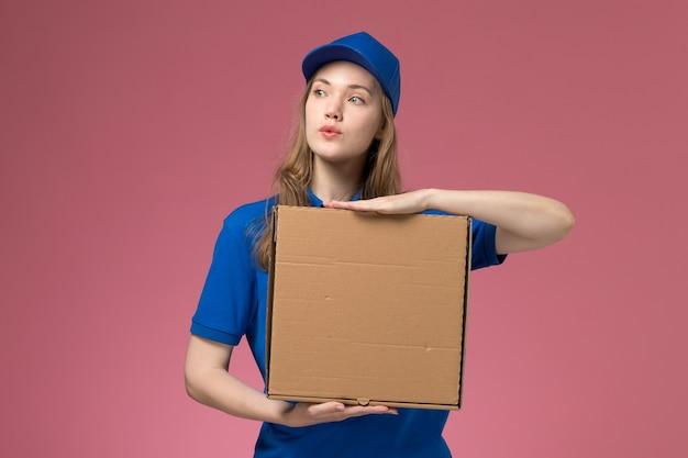 Вид спереди женский курьер в синей форме, держащий коробку для доставки еды на розовом фоне, сервисная форма компании