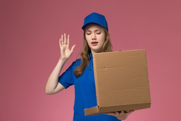 Вид спереди женщина-курьер в синей форме держит коробку для доставки еды на розовом столе.