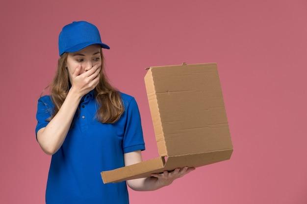 Вид спереди женщина-курьер в синей форме, держащая коробку для доставки еды, открывающую ее с шокированным выражением на розовом рабочем столе, служебная форма, работа компании