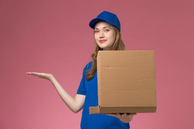 Вид спереди женщина-курьер в синей форме, держащая коробку для доставки еды, позирует с ней на розовом фоне.