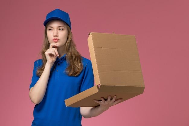 ピンクのデスクワーカーサービス制服会社の仕事を考えて食品配達ボックスを保持している青い制服の正面図女性宅配便