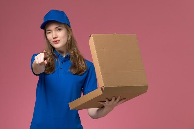 Вид спереди женщина-курьер в синей форме, держащая коробку для доставки еды, подмигивающая розовому рабочему столу, служебная форма, работа компании