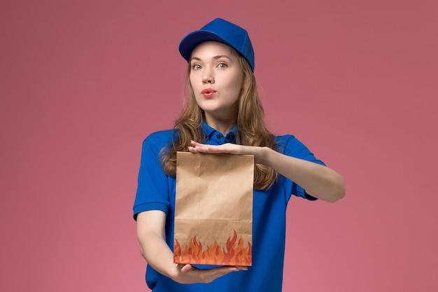 Вид спереди женщина-курьер в синей форме держит пакет с едой на розовом фоне.