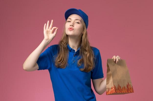 淡いピンクのデスクジョブワーカーサービス制服会社に味のサインを示す食品パッケージを保持している青い制服の正面図女性宅配便