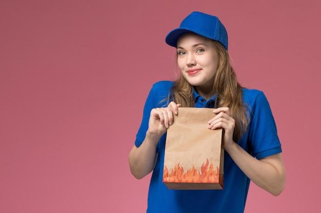 ピンクの背景のジョブワーカーサービス制服会社に微笑みを浮かべて食品パッケージを保持している青い制服の正面図女性宅配便