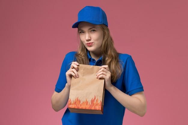 Вид спереди женщина-курьер в синей форме держит пакет с едой со скептическим выражением лица на розовом фоне.