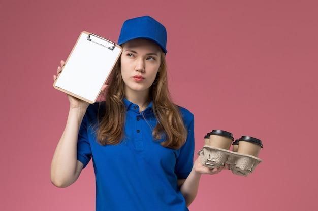 ライトデスクサービスの制服会社の仕事を考えてメモ帳と配達コーヒーカップを保持している青い制服の正面図の女性の宅配便