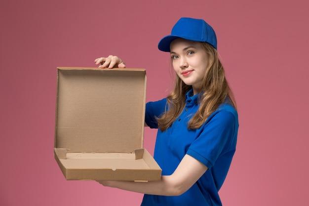 Вид спереди женщина-курьер в синей форме держит открытую и пустую коробку для еды на розовом фоне.