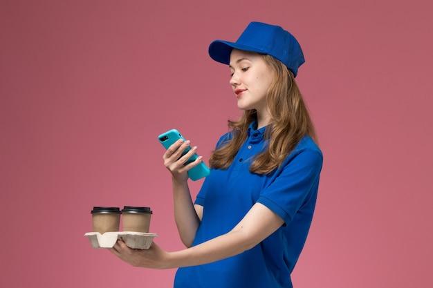 Вид спереди женщина-курьер в синей форме, использующая свой телефон с коричневыми кофейными чашками для доставки на розовом столе, служебная форма, работник компании