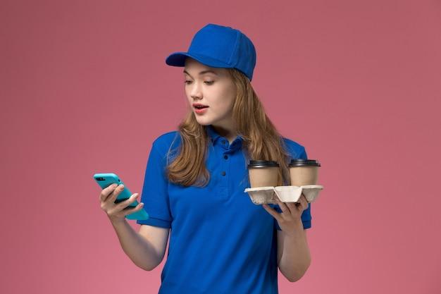 ピンクのデスクサービスの仕事の制服会社で茶色の配達コーヒーカップを保持している彼女の電話を使用して青い制服を着た女性の宅配便の正面図