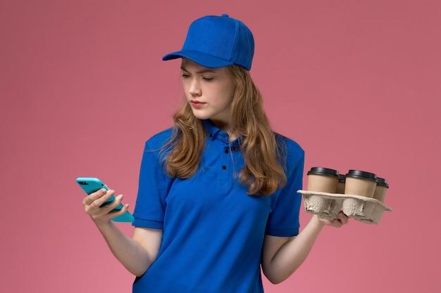 Вид спереди женщина-курьер в синей форме, использующая свой телефон, держащий кофейные чашки доставки на розовом светлом столе, служебная форма, работа компании