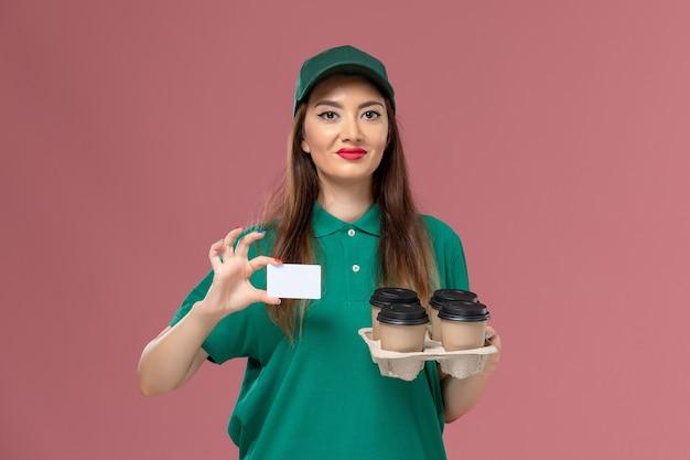 緑のユニフォームとケープホールディングカードの正面図の女性の宅配便とピンクの壁のサービスユニフォーム配達の仕事の労働者の配達コーヒーカップ