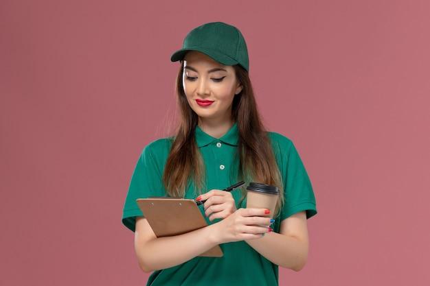 緑のユニフォームと薄ピンクの壁に配達コーヒーカップとメモ帳ペンを保持しているケープの正面図の女性の宅配便会社のサービス仕事の制服の配達