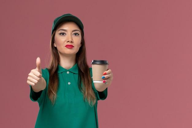 緑の制服を着た正面図の女性の宅配便と淡いピンクの壁に配達コーヒーカップを保持している岬サービスジョブ制服配達