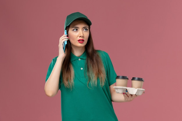 Вид спереди женщина-курьер в зеленой форме и накидке с доставкой кофейных чашек и ее телефоном на розовом столе.