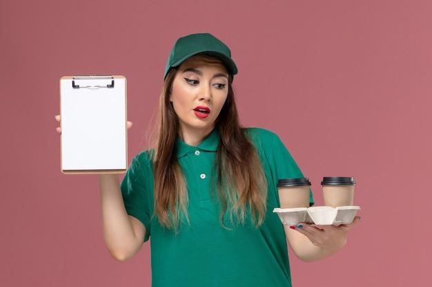Вид спереди женщина-курьер в зеленой униформе и накидке, держащая кофейные чашки и блокнот на светло-розовом столе, доставка рабочей формы