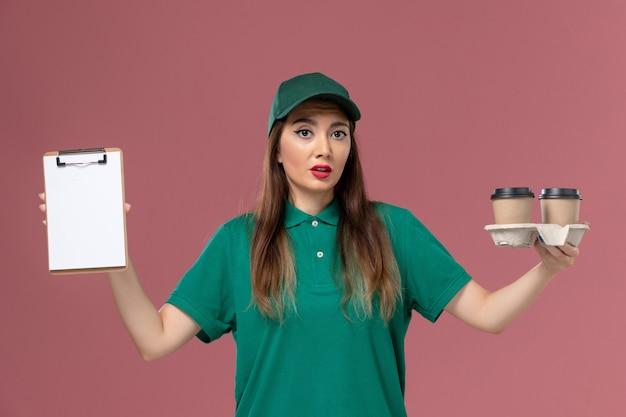 Вид спереди женщина-курьер в зеленой униформе и накидке с кофейными чашками и блокнотом на розовой стене.