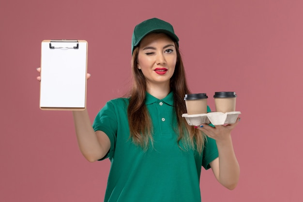 Вид спереди женщина-курьер в зеленой униформе и накидке, держащая кофейные чашки и блокнот на розовой стене, доставка формы работника службы сервиса