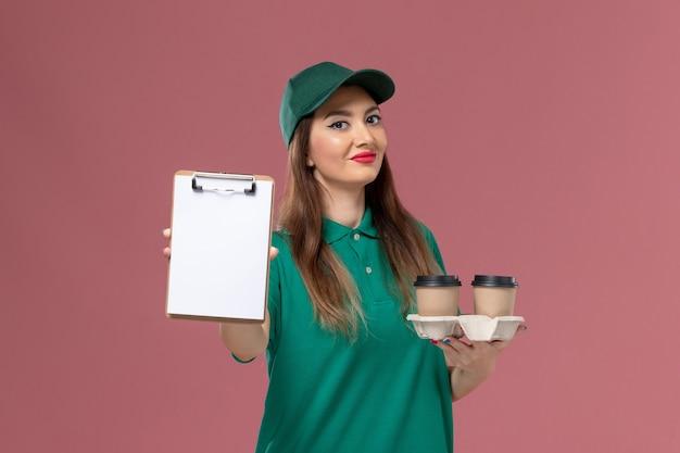 Вид спереди женщина-курьер в зеленой форме и накидке, держащая кофейные чашки и блокнот на розовой стене