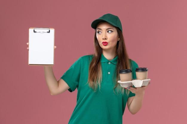 Вид спереди женщина-курьер в зеленой униформе и накидке с чашками кофе и блокнотом, позирующими на розовой стене.