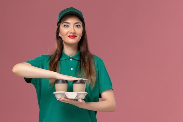 緑の制服と岬の正面図の女性の宅配便は、配達のコーヒーカップを保持し、淡いピンクの壁のサービスの仕事の制服の配達に微笑んでいます