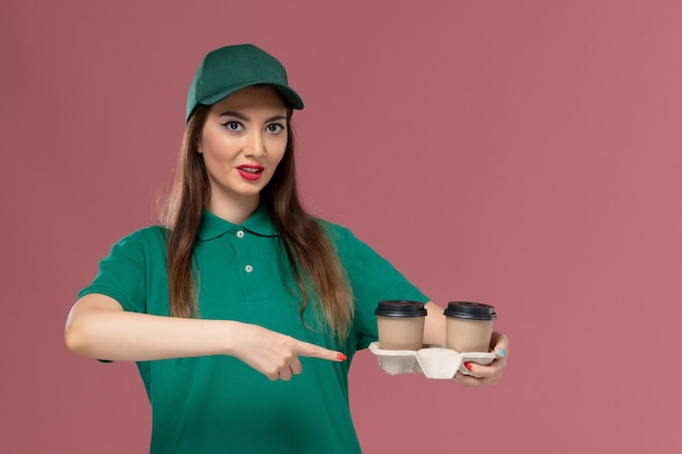緑の制服を着た正面図の女性の宅配便と淡いピンクの壁に配達コーヒーカップを保持しているケープ会社のサービス仕事の制服の配達
