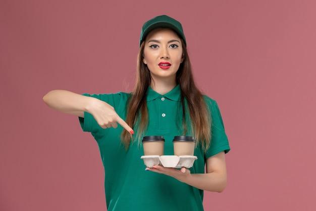 녹색 유니폼과 케이프 핑크 벽 회사 서비스 작업 유니폼 배달 노동자 여성 작업에 배달 커피 컵을 들고 전면보기 여성 택배