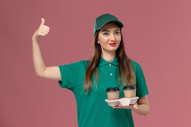 緑の制服を着た正面図の女性宅配便と淡いピンクのデスク会社のサービス制服配達労働者に配達コーヒーカップを保持している岬