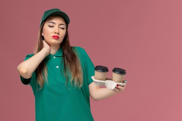 緑のユニフォームと薄ピンクの壁に配達コーヒーカップを保持しているケープの正面図の女性の宅配便会社サービス制服配達