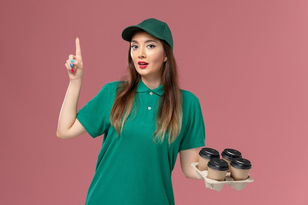 緑の制服とピンクの壁に配達コーヒーカップを保持しているケープの正面図の女性の宅配便サービス制服配達
