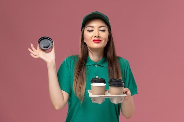 緑の制服を着た正面図の女性の宅配便とピンクの壁のサービスの制服の配達の仕事で臭い配達コーヒーカップを保持している岬