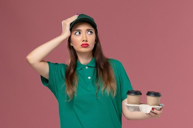 緑の制服を着た正面図の女性の宅配便と淡いピンクの壁の会社のサービスの制服の配達を考えている配達コーヒーカップを保持している岬