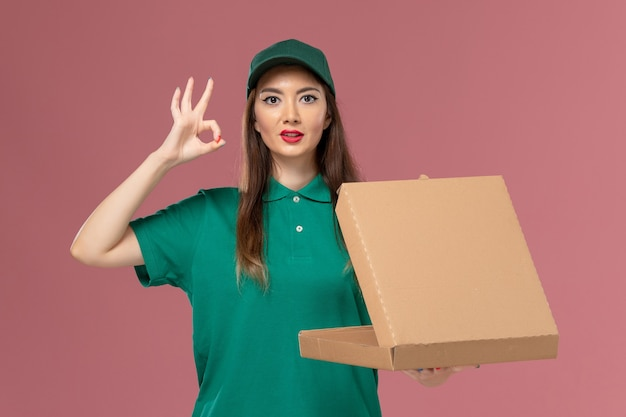 ピンクの壁のサービス制服配達女の子会社に空の食品配達ボックスを保持している緑の制服の正面図女性宅配便