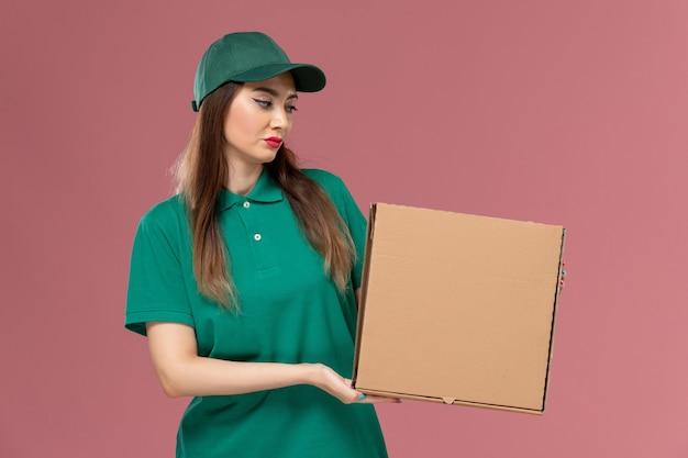 ピンクの壁にフードボックスを保持している緑の制服を着た正面図の女性宅配便労働者サービス制服配達女の子会社