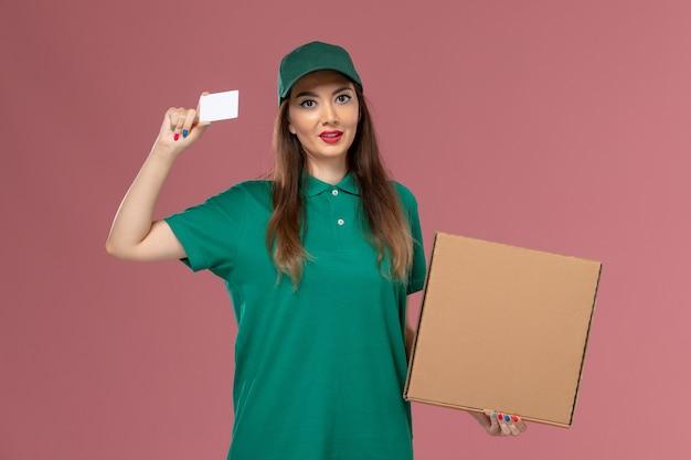 薄ピンクの壁に食品配達ボックスとカードを保持している緑の制服を着た正面図の女性の宅配便会社サービス制服配達の仕事の労働者