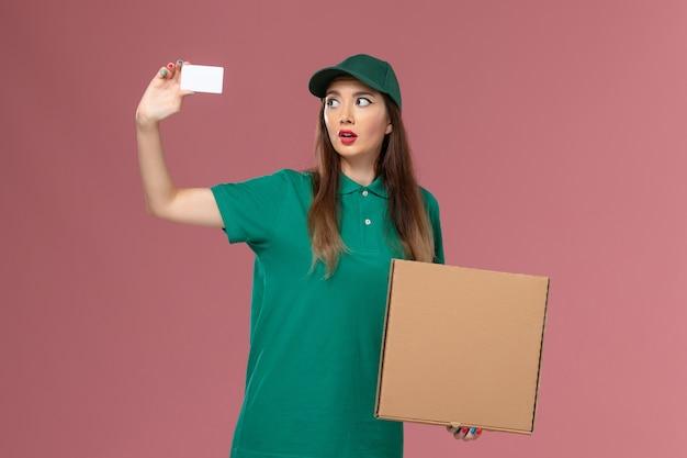 ピンクの壁の会社のサービスの制服の労働者の配達の仕事に食品配達ボックスとカードを保持している緑の制服を着た正面図の女性の宅配便