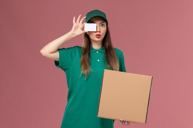 ピンクの壁の会社のサービスの制服の配達作業の仕事で食品配達ボックスとカードを保持している緑の制服を着た正面図の女性の宅配便