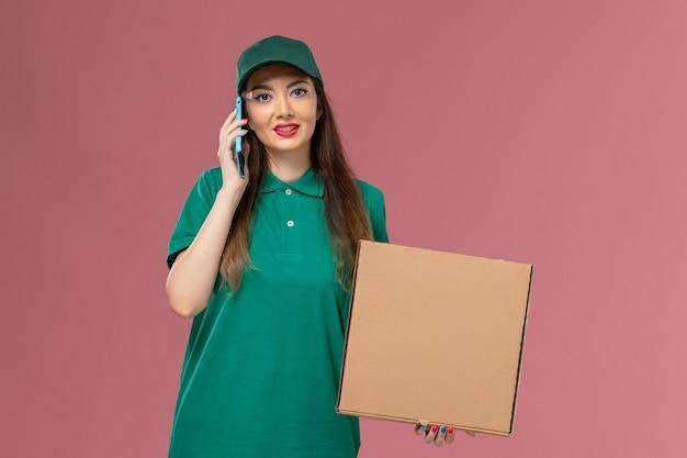 食品配達ボックスを保持し、ピンクの壁の会社のサービスの制服配達で電話で話している緑の制服を着た正面図の女性の宅配便