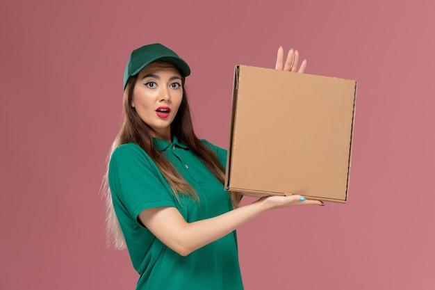 ピンクの壁に食品配達ボックスを保持している緑の制服を着た正面図の女性宅配便労働者サービス制服配達女の子会社