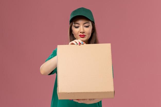 ピンクの壁のサービス制服配達女の子会社の食品配達ボックスを保持している緑の制服の正面図女性宅配便